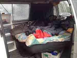 Campervan mit eingebautem Bett, kleinem Regal und Vorhängen